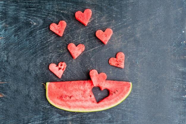 Stuk watermeloen en harten op de oude houten achtergrond. plat liggen