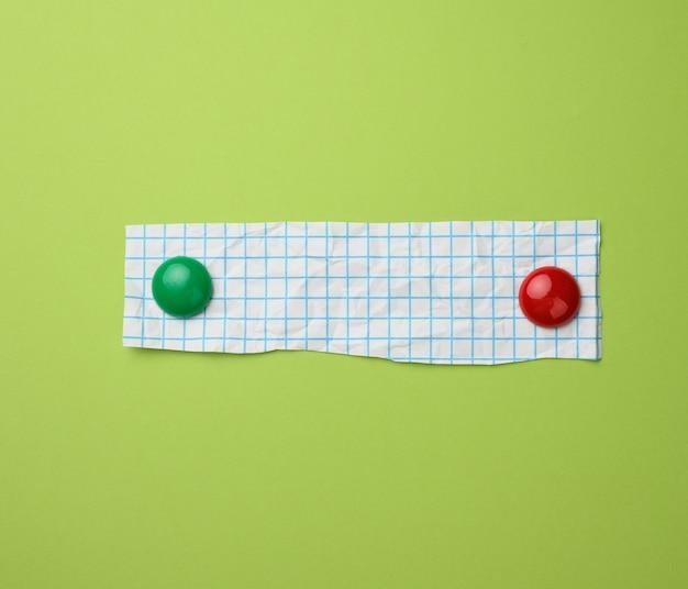 Stuk wit papier in een blauwe kooi op een groene ondergrond. oppervlak voor inscripties