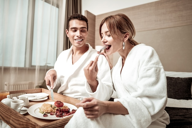Stuk worst. vriend met donkere ogen deelt een stuk worst met zijn geliefde tijdens het ontbijt in het hotel