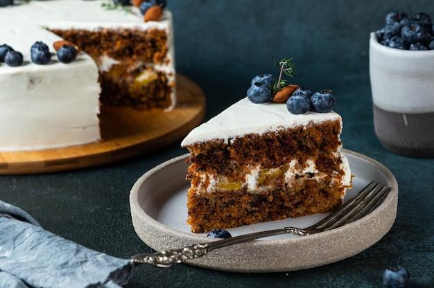Stuk worteltaart met walnoten en bosbessen op donkere houten ondergrond. lokaal eten. traditionele amerikaanse cake. taart voor thanksgiving day. herfst taart.