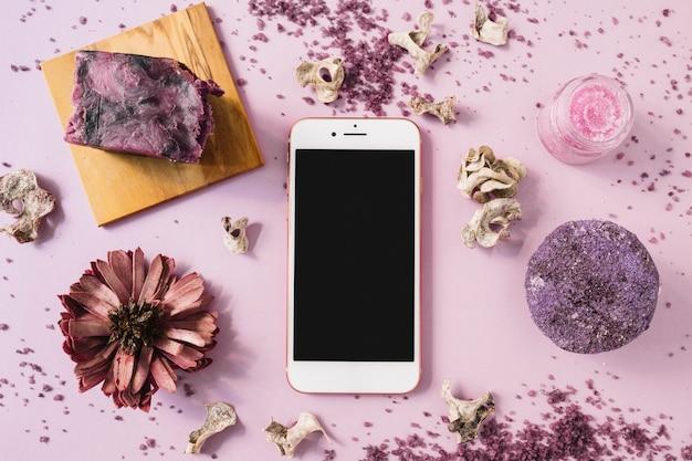 Stuk zeep; kruidenlichaam scrub; gedroogde bloem en smartphone op roze achtergrond