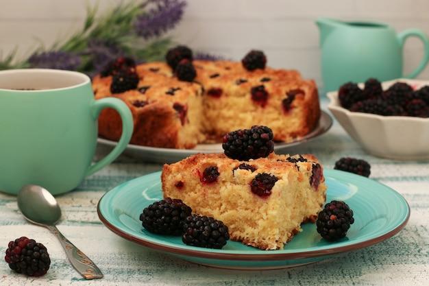 Stuk zelfgemaakte taart met bramen en kokoschips op een lichtblauwe ondergrond. detailopname
