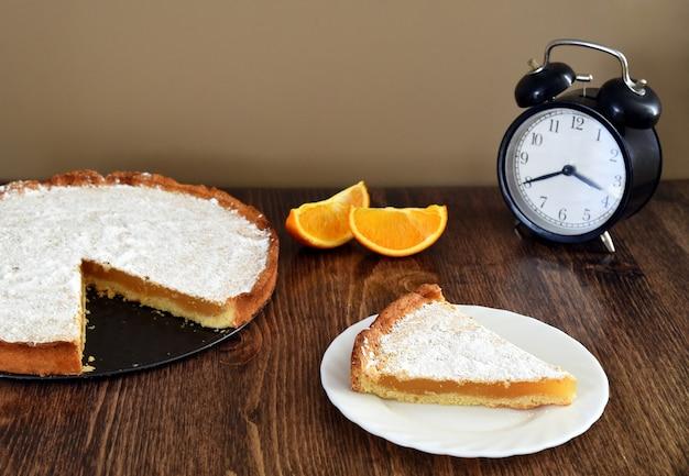Stuk zelfgemaakte taart met citroen en sinaasappel vulling op houten tafel