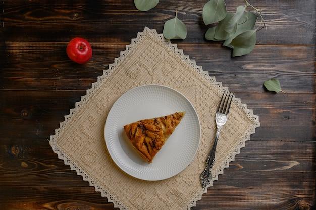Stuk zelfgemaakte traditionele appeltaart uit cornwall op een witte plaat met een vork op een servet.
