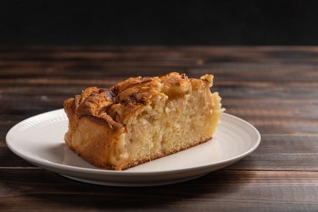 Stuk zelfgemaakte traditionele appeltaart uit cornwall op een witte plaat op de beboste tafel. detailopname. rustieke stijl. ruimte kopiëren