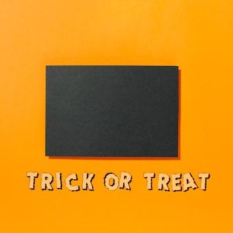 Stuk zwart papier met trick or treat-inscriptie hieronder