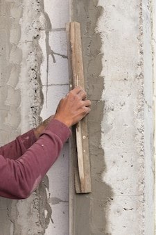 Stukadoor concrete werknemer bij muur van huisbouw