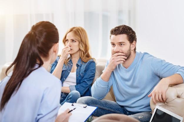 Stukje advies. nadenkende, aangename jongeman die zijn kin vasthoudt en naar de psycholoog luistert terwijl hij het probleem bespreekt