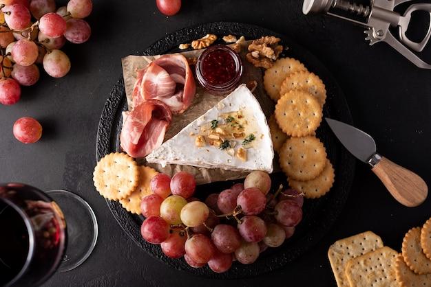 Stukje brie kaas met druiven, crackers en rode wijn