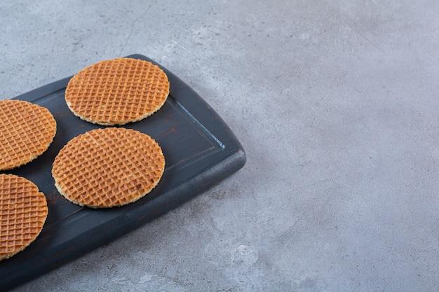 Stukje bruine zelfgemaakte stroopwafelsnacks in een houten bord