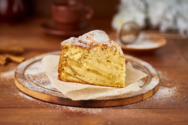 Stukje franse appeltaart met appels, kaneel op donkere houten keukentafel
