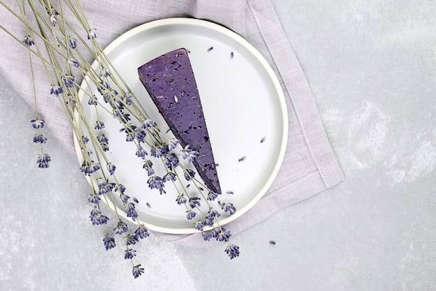 Stukje paarse kaas met droge basilicum en lavendelbloemen in plaat op grijze betonnen tafelbladweergave