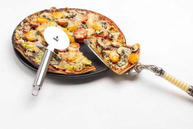 Stukje pizza op schep. klaar pizza op zwarte plaat. pizzasnijder op pizza. kopieer ruimte. wit oppervlak. bovenaanzicht