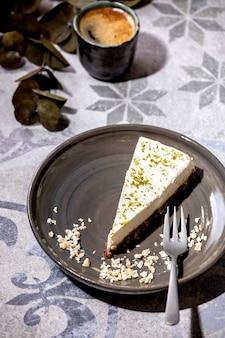 Stukje rauwe vegan cheesecake, niet gebakken glutenvrij, gedecoreerd met limoenschil en cashewnoten op bord