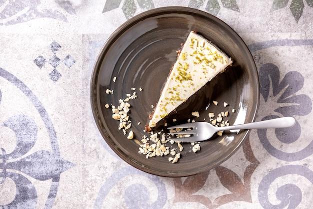 Stukje rauwe vegan cheesecake, niet gebakken glutenvrij, gedecoreerd met limoenschil en cashewnoten op plaat op sierlijke keramische tafel