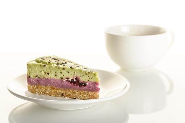 Stukje rauwkost cake met kiwi en bramen op een witte kop achtergrond.