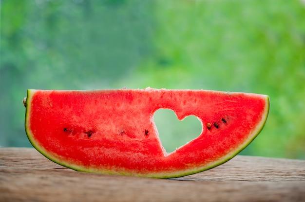 Stukje watermeloen met hart op de achtergrond van groen. plat liggen