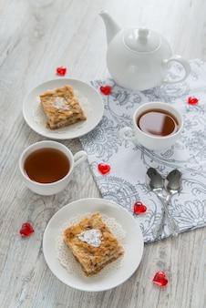 Stukjes appeltaart met kopjes thee