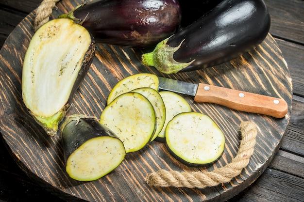 Stukjes aubergine op een snijplank met een mes. op houten tafel