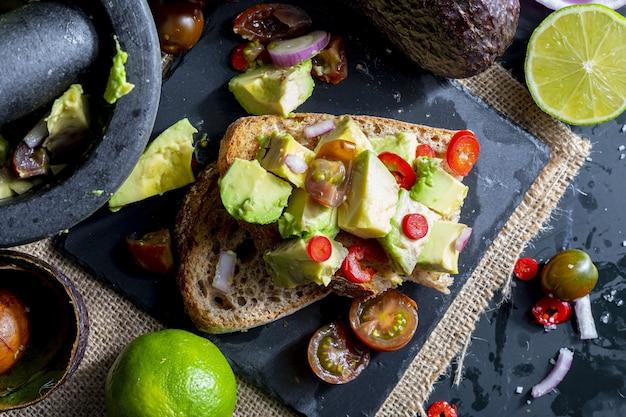 Stukjes avocado, ui, chili en limoensap op toast