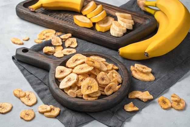 Stukjes bananenchips op een muur van verse banaan op een grijze muur. zijaanzicht.