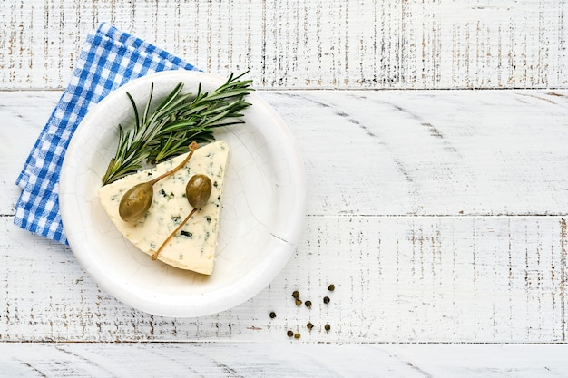 Stukjes blauwe kaas of brie kaas in een kom met rozemarijn, kappertjes en peper.