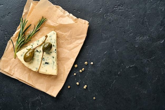 Stukjes blauwe kaas of brie op een stuk bakpapier met honing, rozemarijn, kappertjes en peper