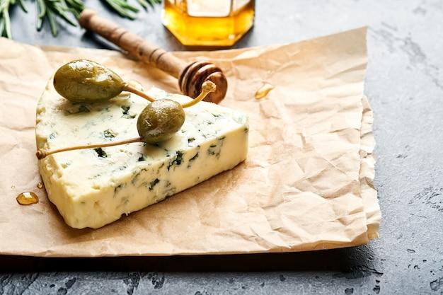 Stukjes blauwe kaas of brie op een stuk bakpapier met honing, rozemarijn, kappertjes peper