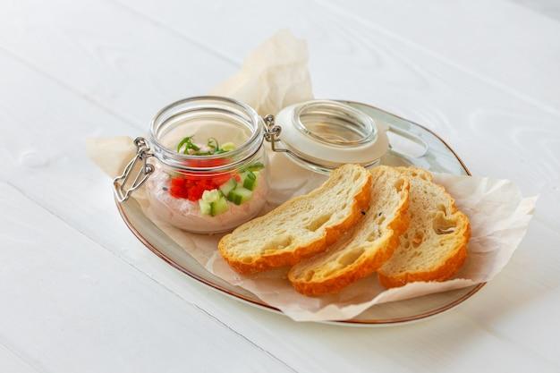 Stukjes brood met vispastei op wit wordt geïsoleerd