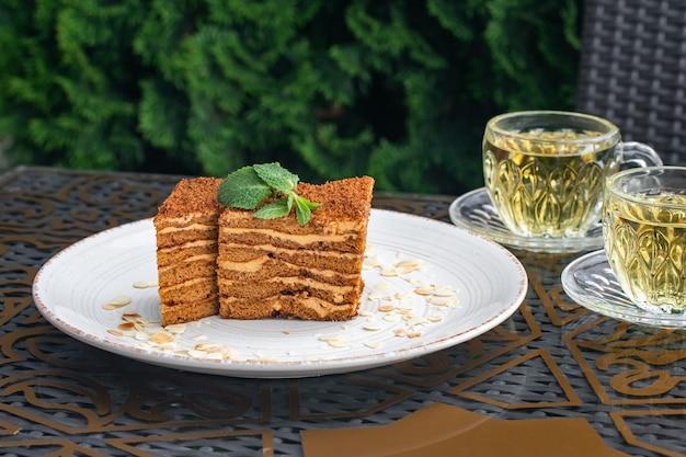 Stukjes cake en twee glazen kopjes muntthee. medovik cake op een tafel in een zomercafé. thee drinken concept, russische cultuur. stilleven. huisgemaakt honingdessert.