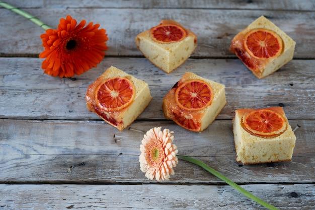 Stukjes cake met bloedsinaasappel en twee bloemen