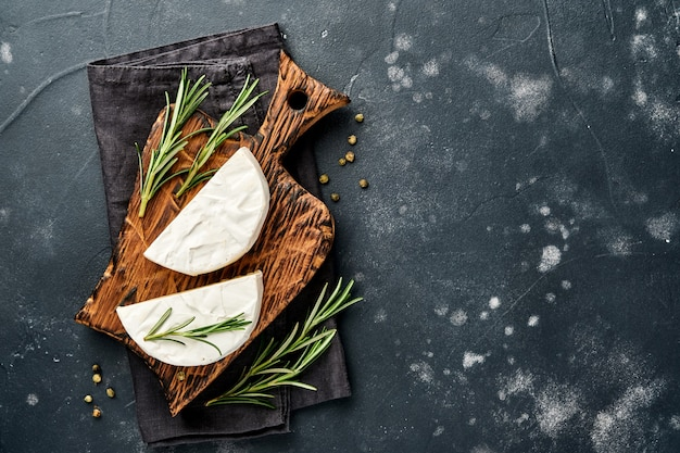 Stukjes camembert kaas met rozemarijn, kappertjes en peper. op zwarte oude achtergrond.