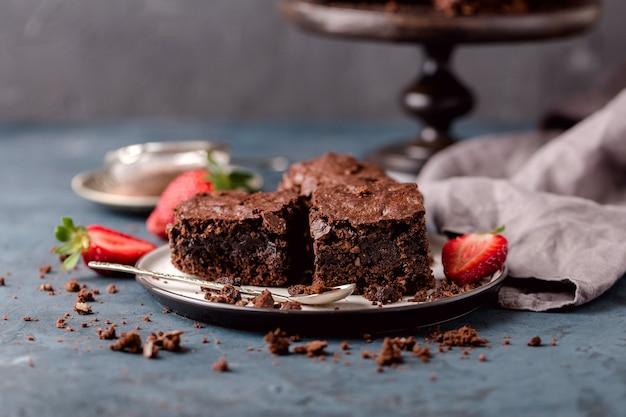 Stukjes chocolade noten brownie, op schotel met plakjes aardbeien, kruimels. blauwe, grijze achtergrond. horizontaal