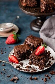 Stukjes chocolade noten brownie, op witte plaat, lepel, met plakjes aardbeien, kruimels, grijs textiel. donkerblauwe achtergrond. verticaal