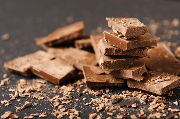 Stukjes chocoladereep gestapeld met chocoladeschilfers op een zwarte achtergrond