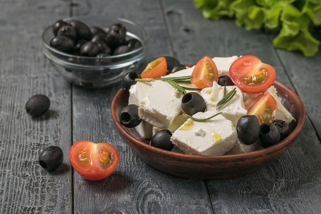 Stukjes fetakaas met olijven en tomaten in een kleikom. salade met kaas en groenten.