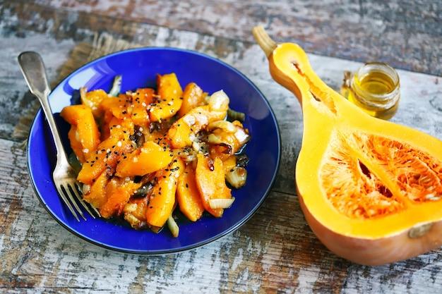 Stukjes gebakken pompoen met uien op een blauw bord pompoenrecept herfstvoedsel