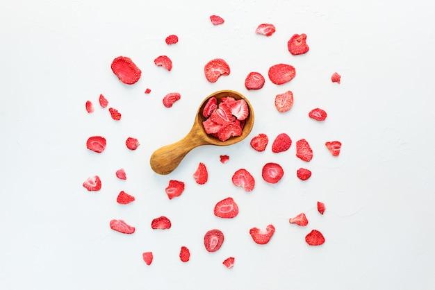Stukjes gedroogde aardbeien met een houten lepel op een wit