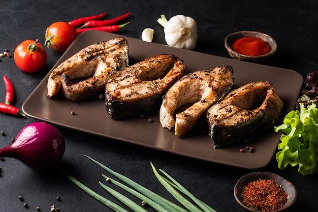 Stukjes gegrilde karper op een bord met tomites paprika rode ui knoflook