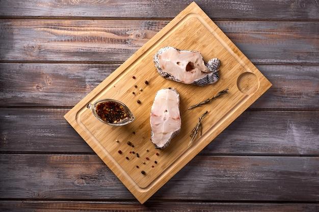 Stukjes gesneden witte rauwe vis olijfolie rozemarijn peper op houten snijplank op houten rustieke