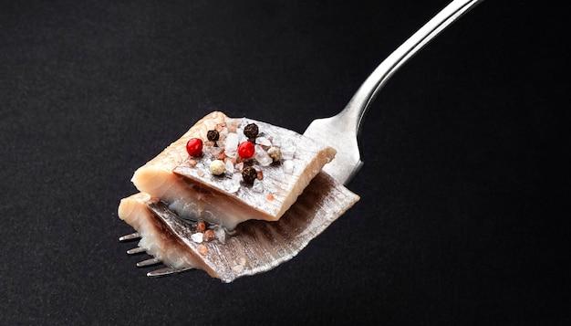 Stukjes gezouten haring op vork op zwarte achtergrond, plakjes gemarineerde makreel visfilet met zout en kruiden