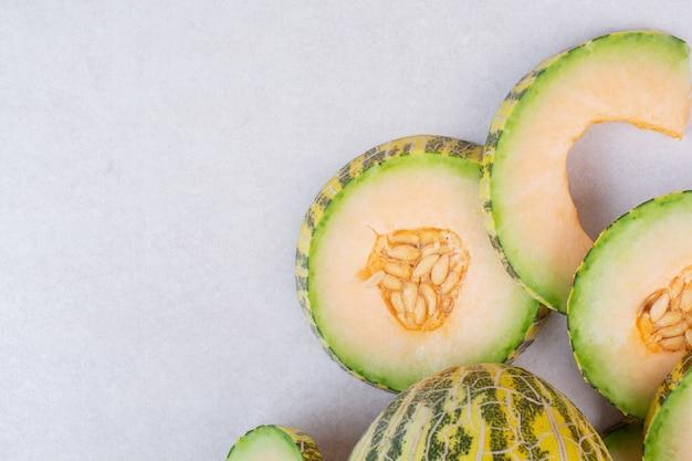 Stukjes groene meloen op wit.