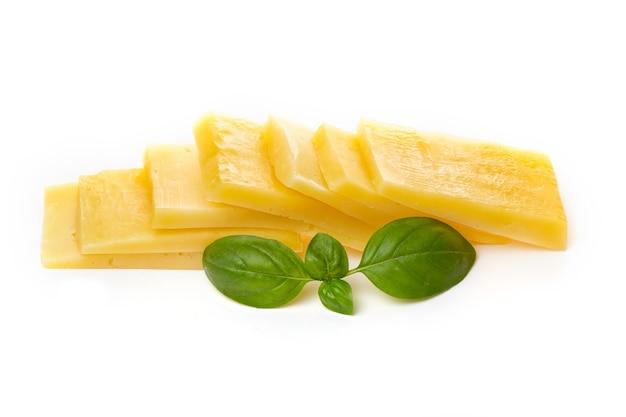 Stukjes halfharde of harde gele kaas met gaten en basilicumblad geïsoleerd op een witte achtergrond.