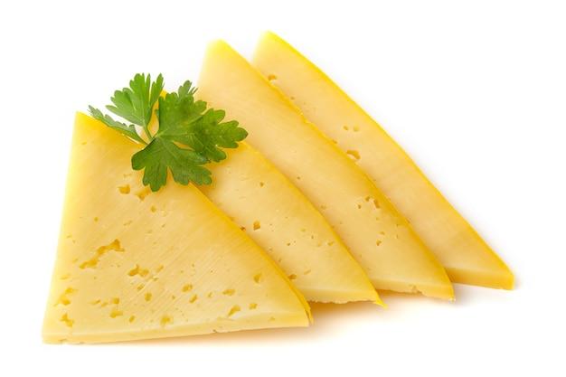 Stukjes halfharde of harde gele kaas met gaten en peterselieblad geïsoleerd op een witte achtergrond.
