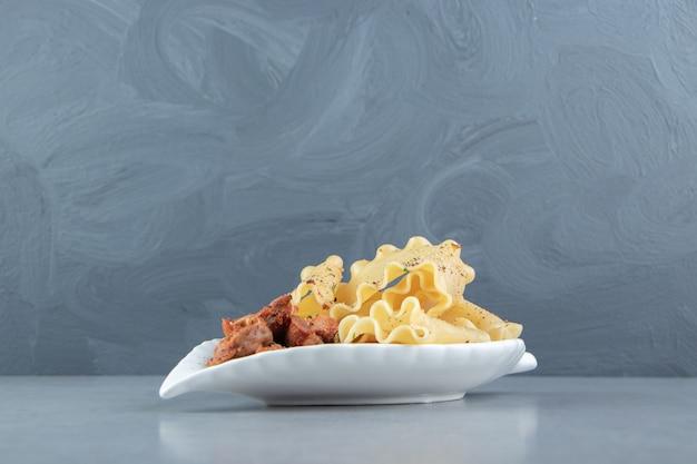 Stukjes kip en pasta op bladvormige plaat.