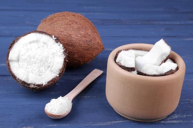 Stukjes kokosnoot in een houten kom met een lepel met een grote hele kokosnoot op een blauwe houten achtergrond.
