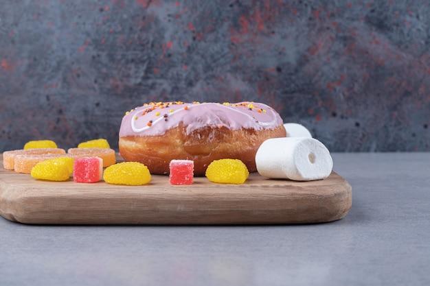 Stukjes marmelade, marshmallows en een donut op een houten bord op een marmeren oppervlak