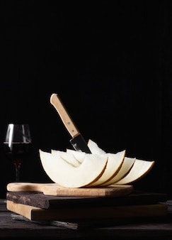 Stukjes meloen op houten planken met een mes, een glas wijn op de achtergrond. rustieke stijl.