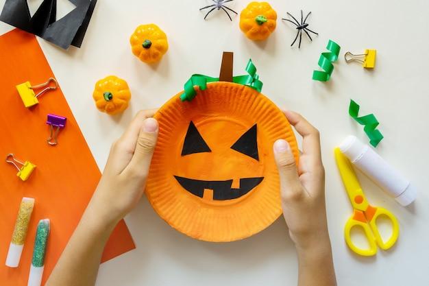 Stukjes papier voor halloween. handgesneden papier. pompoenen. schaar en lijm. op een lichte achtergrond. bovenaanzicht. plat leggen. doe-het-zelf. stap voor stap. snoep of je leven.