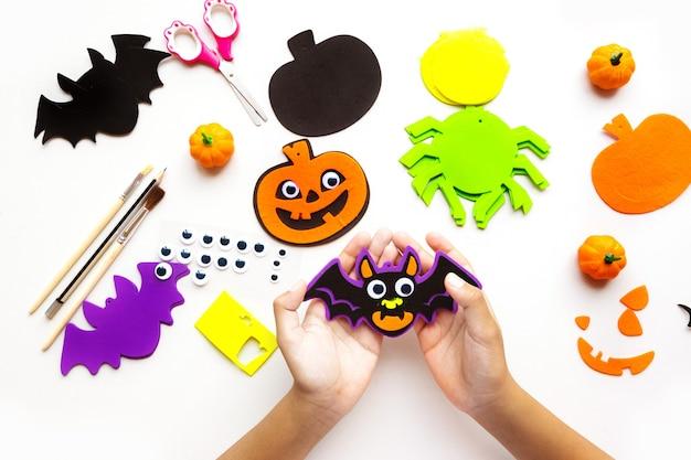 Stukjes papier voor halloween. handgesneden papier. pompoenen. schaar en lijm. op een lichte achtergrond. bovenaanzicht. plat leggen.